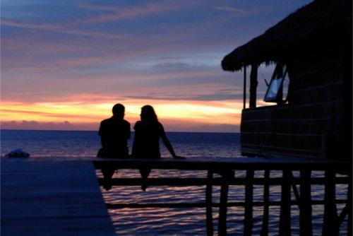 couple sitting under sunset