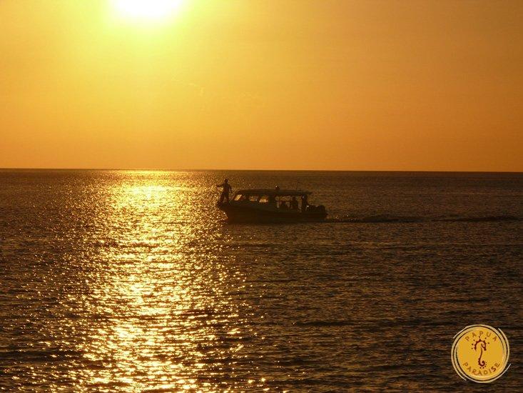 Papua paradise boat under sunset